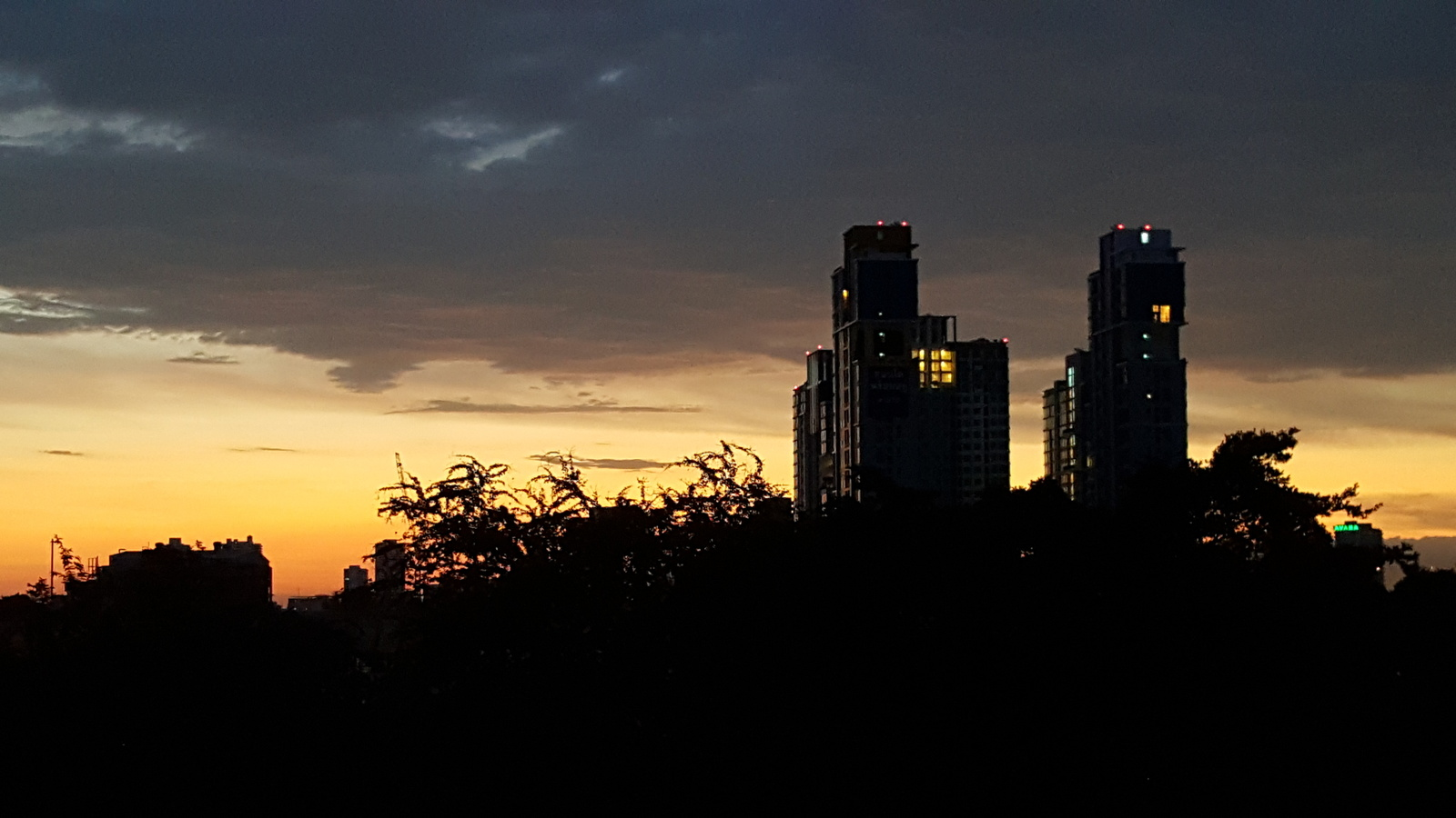 A couple of tall buildings silhoetted against the first light of dawn