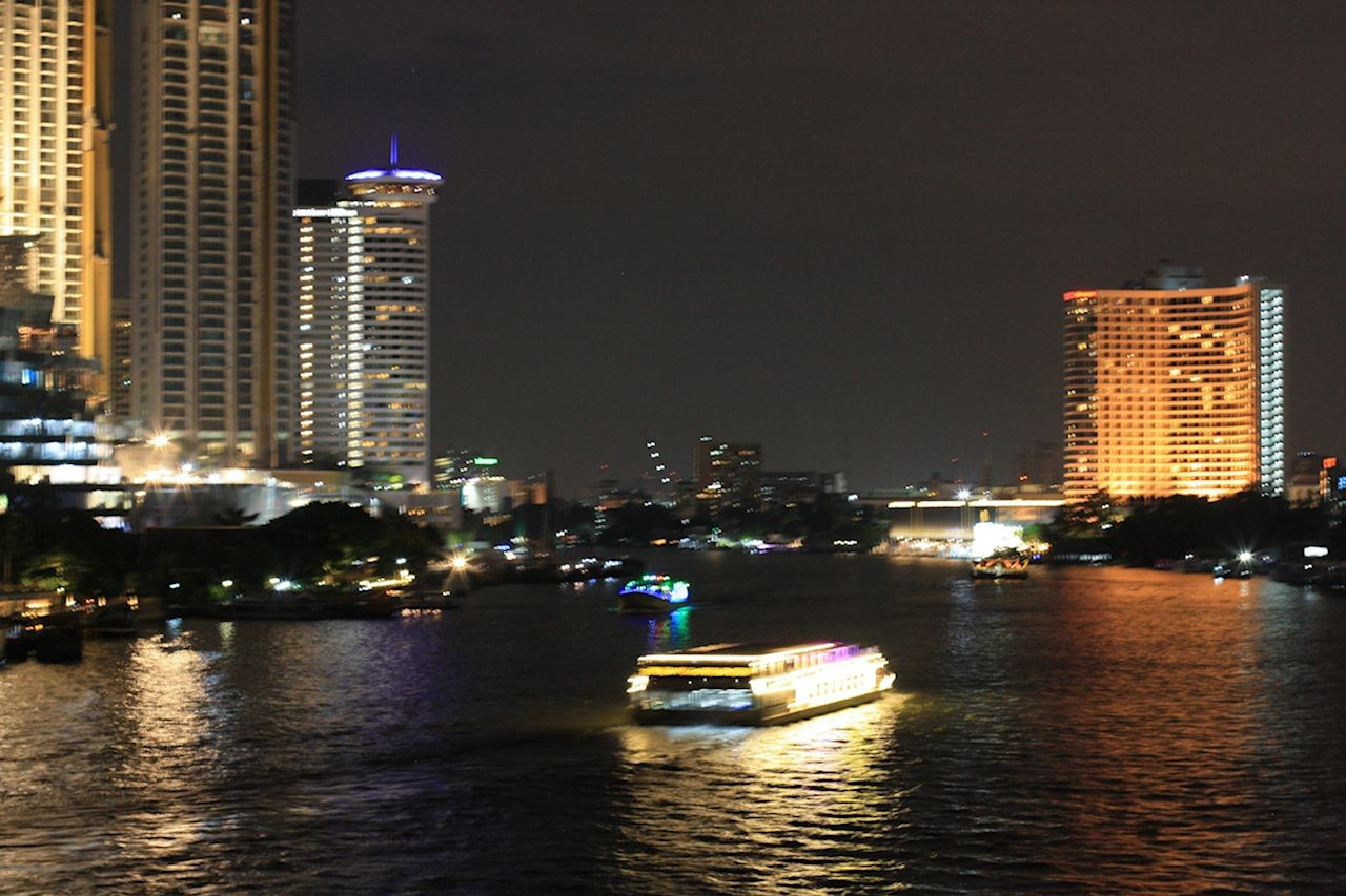 Bangkok night scene with high rise buildings and a ferry boat on the Jao Praya River.jpg
