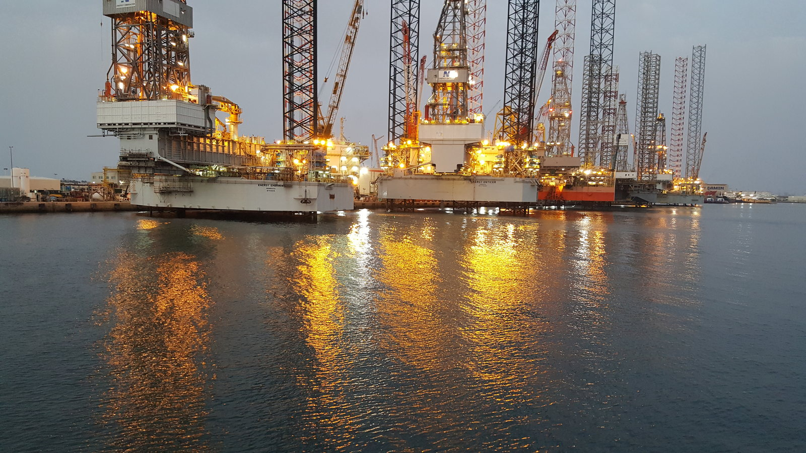 Oil rigs at Hamriyah with their lights reflecting in the water